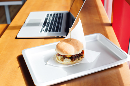 Eating at work place - fast food. burger near laptop. lunch break while you work or sharing online