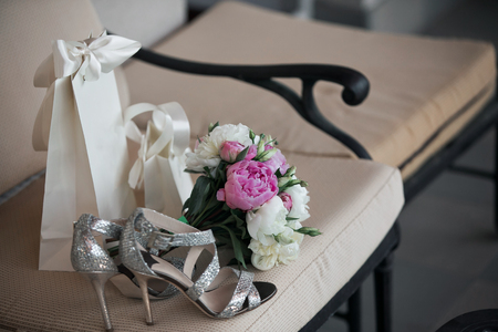 pion: Wedding. Bouquet of pink, white flowers and greenery is in a chair against next to the brides shoes Stock Photo