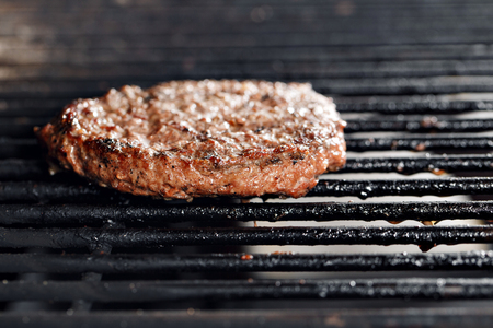 Beef Burger And Spatula On The Hot Flaming BBQ Charcoal Grill, Close-up Stock Photo
