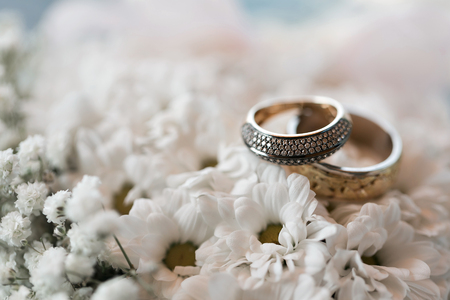 Wedding rings on a white flowers pillow. accessories wedding closeup. selective focus Stock Photo