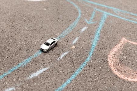 toy car on a asphalt. chalk painted road markings. right-hand movement, rotation and strip