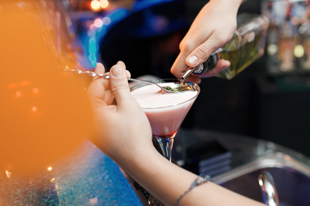 adding: Bartender is adding ingredient in glass at bar counter, at night club. Stock Photo