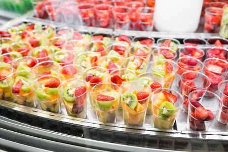 Fresh fruit mix in plastic cups on market showcase