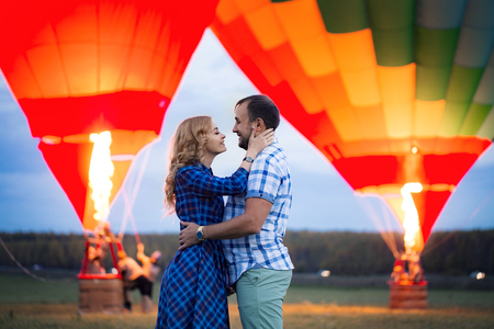 Beautiful romantic couple hugging at meadow. hot air balloon on a background