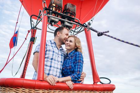 adventure. Beautiful romantic couple hugging in bascket hot air balloon