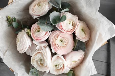 Bouquet of light pink ranunculus in vase on wooden background