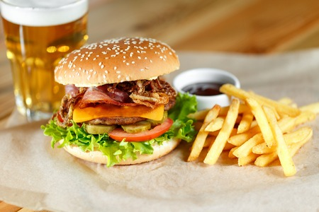 beefburger: Big tasty burger and fries with beer on backround on the wooden table Stock Photo