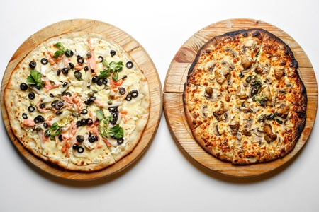 Burnt and normal. Two pizza with tomatoes, salmon, mushroom, pepperoni on wooden rustic background top view