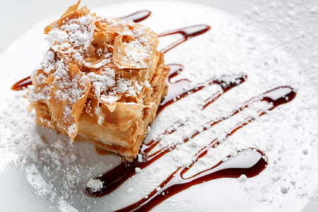 cake Napoleon on a white plate, on a wooden background. Balsamic cream