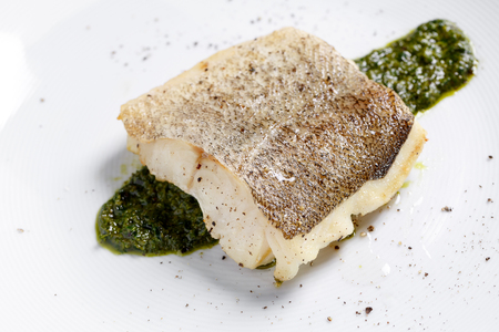 Fried fish fillet, Atlantic cod with rosemary in white plate Standard-Bild