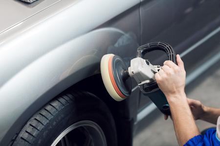 워크샵에서 회색 차체를 연마하기 위해 폴리 셔를 사용하는 손 작업자의 근접 스톡 콘텐츠