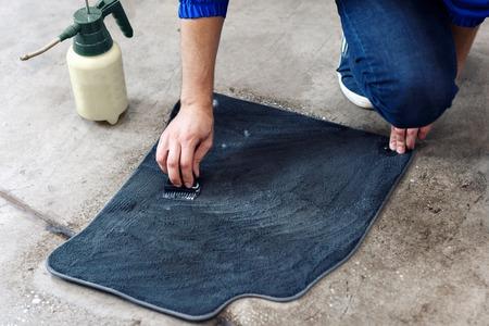自動車クリーニング - の詳細車の床をきれいにする専門的な化学ソリューションを使用して男性マットします。 写真素材