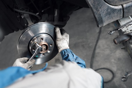 Car mechanic hands replace brakes in garage.