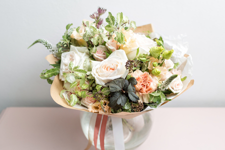 cute light bouquet with garden roses and mixed flowers on pink table Imagens