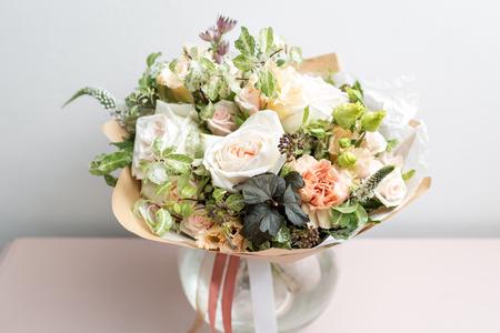 schattig licht boeket met tuinrozen en gemengde bloemen op roze tafel Stockfoto