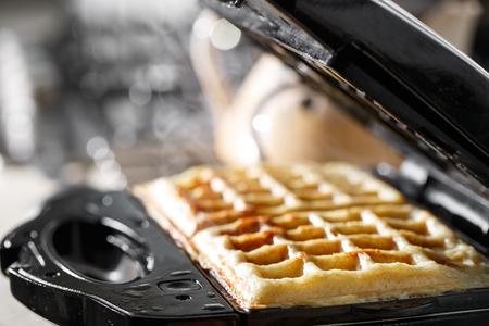 철제 와플 메이커에서 갓 구운 전통적인 벨기에 와플