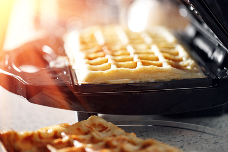 Freshly baked traditional Belgian waffles in iron waffle maker