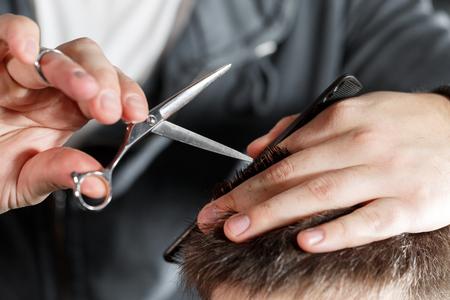 barbershop: mens haircut with scissors at salon