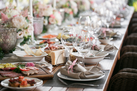 Decorated table, a plate of neatly arranged napkin, fork and knife. Beautifully decorated table with white plates, crystal glasses, linen napkin. Stock Photo
