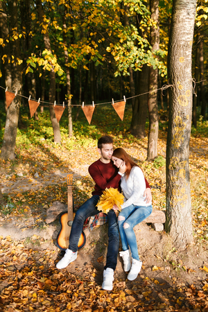 autumn picnic. Happy couple with guitar near the tent.