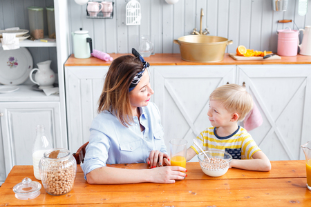 niños desayunando: Mother and son are smiling while having a breakfast in kitchen. look at each other