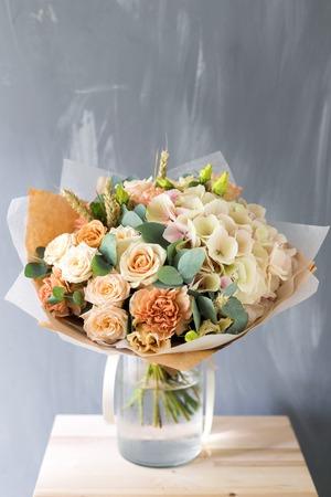 Bloemige compositie met rozen en mix bloemen in glazen vaas op een grijze achtergrond. Stockfoto - 85569907