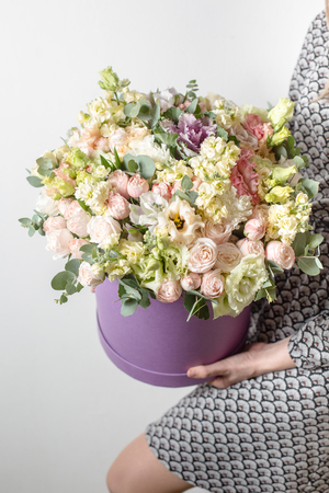 Luxury bouquets of mix flowers in the hat box. in the girls hands