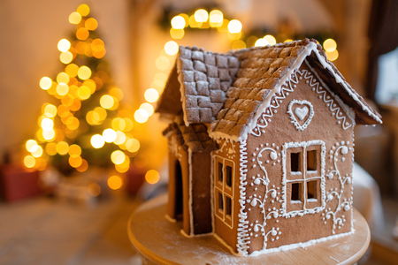 gingerbread house over defocused lights of Chrismtas decorated fir tree