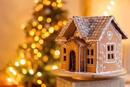 Peperkoek huis over intreepupil lichten van Chrismtas versierde dennenboom Stockfoto - 88360406