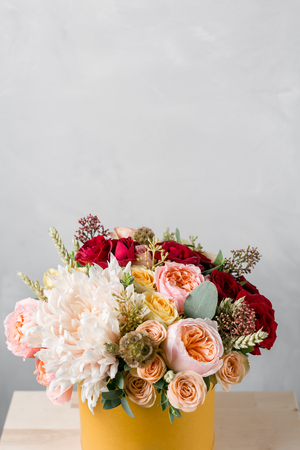 Flowers in round luxury present box. Bouquet of mixed flowers in yelow paper box.