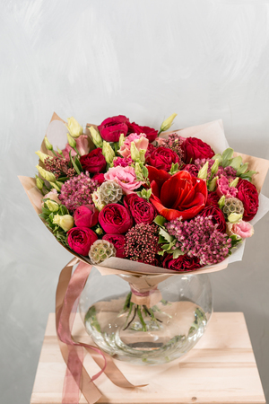 beautiful bouquet of mixed flowers into a vase on wooden table