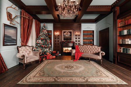 Christmas evening. classic apartments with a white fireplace, decorated tree, sofa, large windows and chandelier.