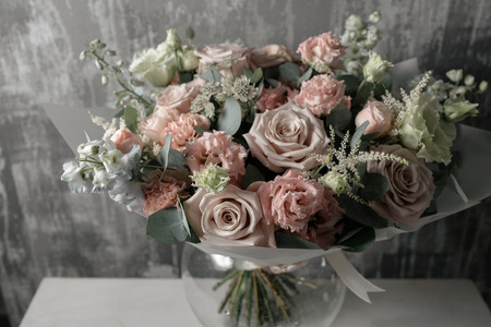 beautiful bouquet of mixed flowers into a vase on wooden table. copy space
