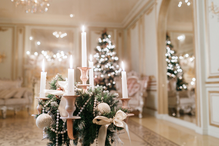 the chandelier with candles in the foreground. Christmas evening. classic apartments with a white fireplace.