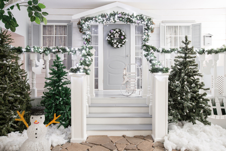 house entrance decorated for holidays. Christmas decoration. garland of fir tree branches and lights on the railing Stock Photo