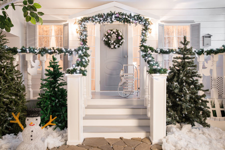 house entrance decorated for holidays. Christmas decoration. garland of fir tree branches and lights on the railing Foto de archivo