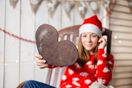 Christmas or New Year celebration. Happy woman sitting in the rocking chair. Holding a heart figure out of wood. selective focus and copy space
