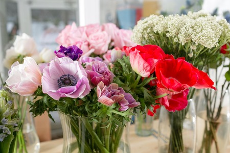 different varieties. Fresh spring flowers in refrigerator for flowers in flower shop. Bouquets on shelf, florist business.