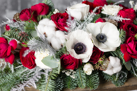 Winter decor. The composition of the branches Nobilis and fresh flowers. Work florist in shop. For decorating a family dinner Stock Photo