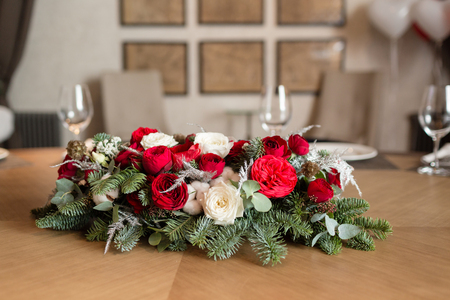 Winter decor. The composition of the branches Nobilis and fresh flowers. For decorating a family dinner