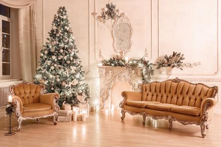 Tarde navideña a la luz de las velas. Apartamentos clásicos con chimenea blanca, árbol decorado, sofá, grandes ventanales y araña.