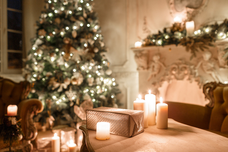 the gifts on the table. Christmas evening by candlelight. classic apartments with a white fireplace, decorated tree, sofa, large windows and chandelier. Stock fotó