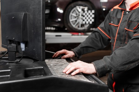 auto mechanic performs diagnostics and configuration on the computer . Wheel alignment equipment on a car wheel in a repair station Standard-Bild