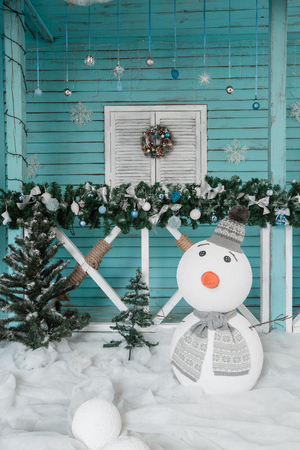 Christmas snowman decoration. The terrace with fir garlands