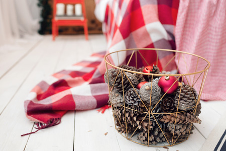 Christmas decorations in basket and pine cones on floor close up. Imagens