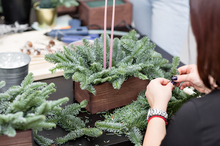 Workshop of Christmas decor with their own hands. Christmas wooden box with fir branches for the holiday. The new year celebration. Master class on making decorative ornaments Stock Photo