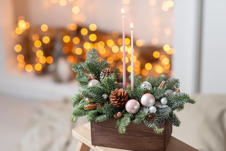 ablaze candles. Workshop of Christmas decor with their own hands. Christmas wooden box with fir branches for the holiday. The new year celebration.