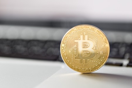 munt bitcoin op het toetsenbord van de laptop. het concept van het verhandelen van cryptocurrency. De snelle groei van de valuta. Stockfoto