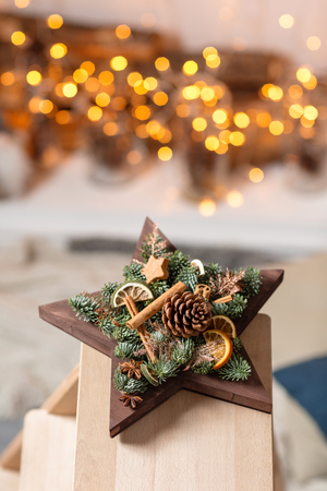 Workshop of Christmas decor with their own hands. Christmas wooden box star with fir branches for the holiday. The new year celebration.