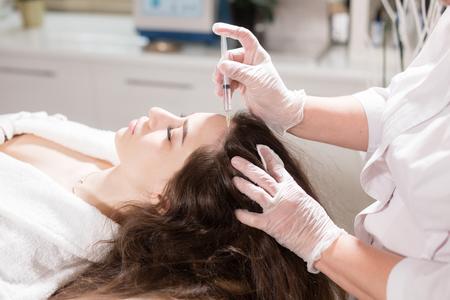 Belle femme reçoit une injection dans la tête. La procédure fait médecin dans les gants blancs. Le concept de mésothérapie Pousser pour renforcer les cheveux et leur croissance